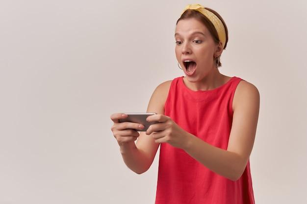 Mulher com maquiagem natural e brincos usando vestido vermelho na moda elegante e bandana amarela posando de emoção na parede, alegria, jogando jogo animado olhando para o telefone