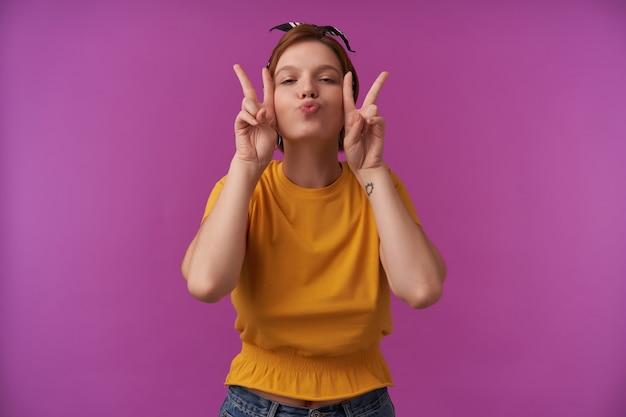 Mulher com maquiagem natural usando blusa amarela elegante de verão e bandana preta com dois dedos emoção alegre flertando olhos fechados beijo lábios na parede roxa