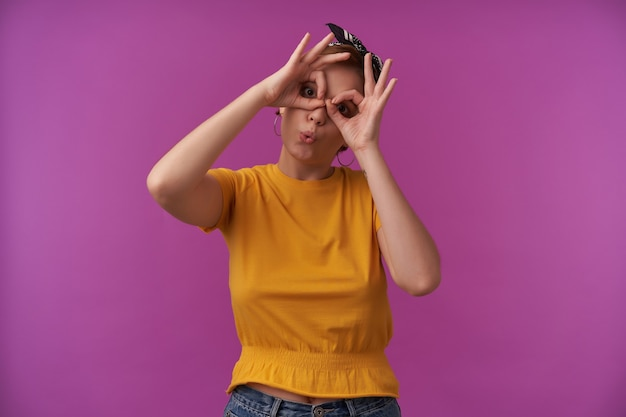 Mulher com maquiagem natural vestindo blusa da moda e bandana preta com os braços no rosto mostrar óculos batman dedos emoção alegria brincar bobo posando na parede roxa