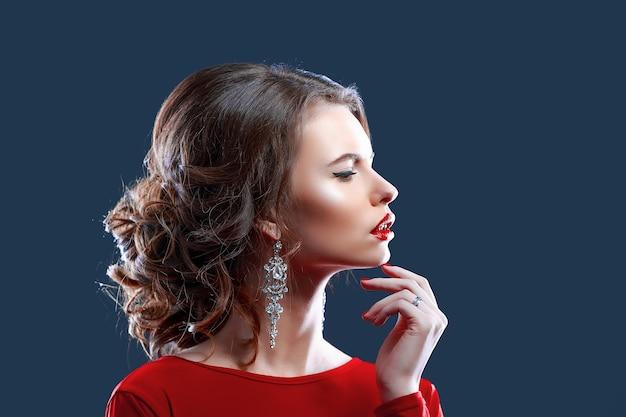 Mulher com maquiagem, penteado, vestido vermelho, posando com copo de videira sobre fundo escuro