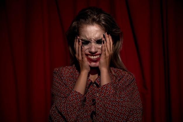 Mulher com maquiagem sangue no rosto chorando