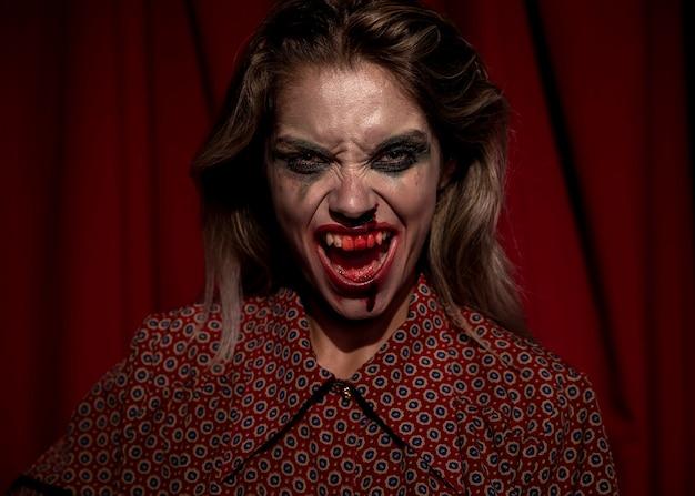 Mulher com maquiagem sangue no rosto gritando