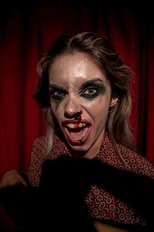 Mulher com maquiagem sangue no rosto, olhando para a câmera