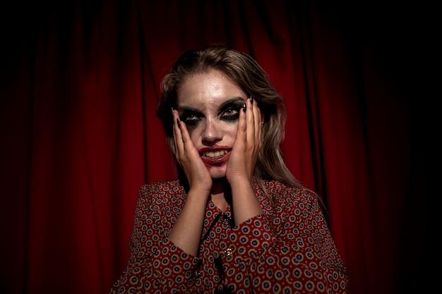 Mulher com maquiagem sangue no rosto, segurando sua cabeça