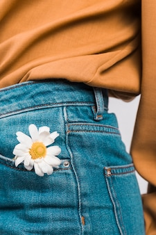 Mulher, com, margarida, flor, em, calças brim, bolso