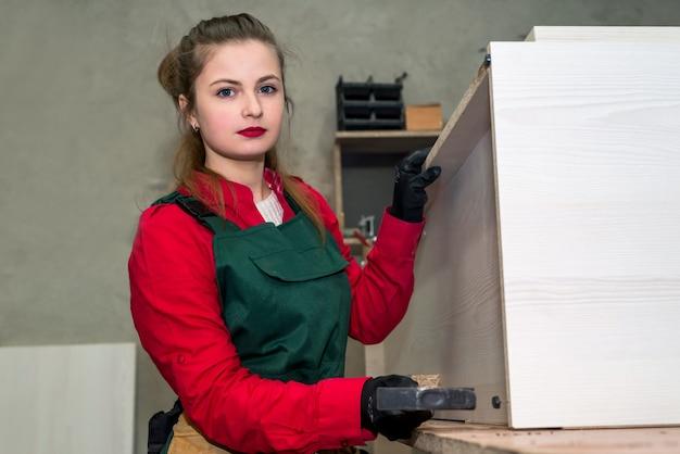 Mulher com martelo construindo móveis em carpintaria