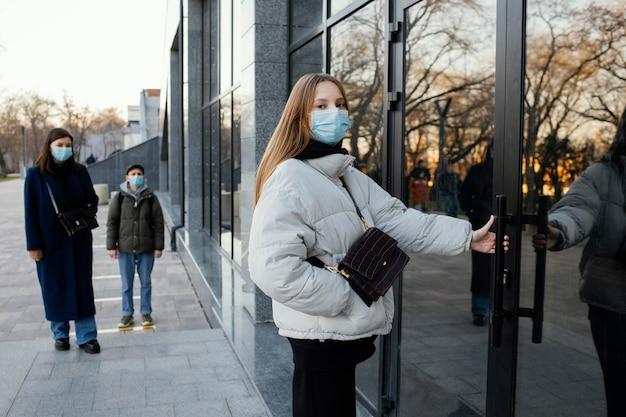 Mulher com máscara abrindo porta