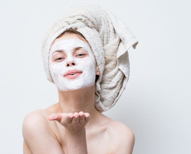 Mulher com máscara contra pontos pretos nas emoções do rosto com uma toalha na cabeça limpa a pele