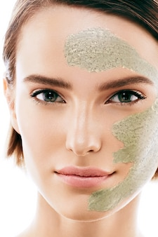 Mulher com máscara cosmética no rosto. tiro do estúdio. isolado no branco.