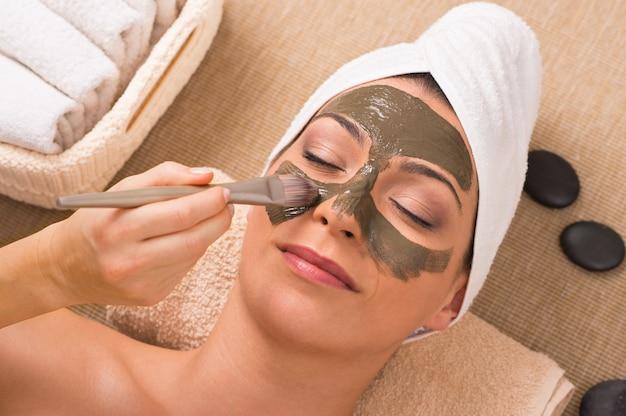 Mulher com máscara de argila verde no spa