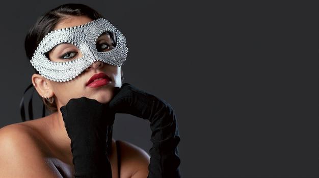 Mulher com máscara de carnaval de frente