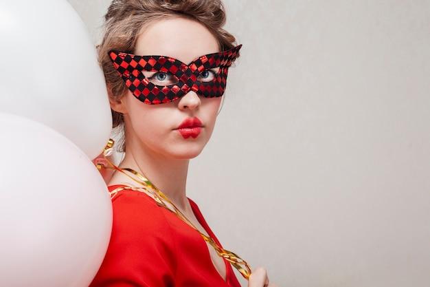 Mulher com máscara de carnaval e balões tiro médio
