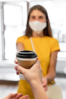 Mulher com máscara de comprar café