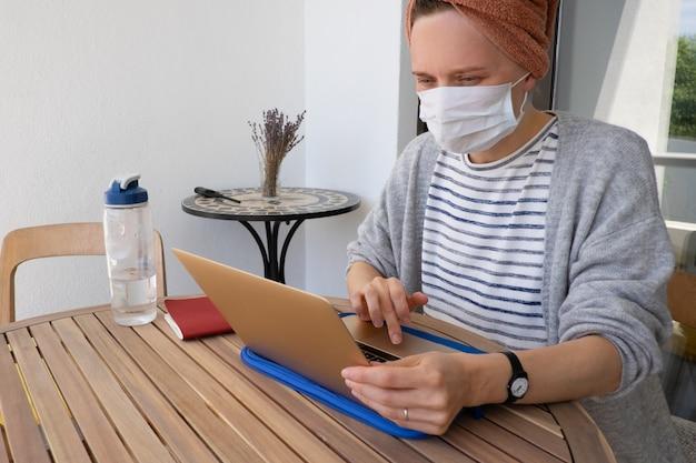 Mulher com máscara de medicina trabalhando com laptop