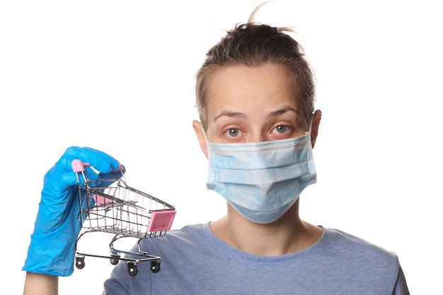 Mulher com máscara de mídia e luvas segurando carrinho de compras isolado no branco