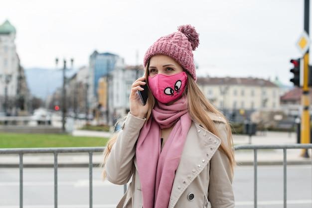 Mulher com máscara de moda usando seu telefone