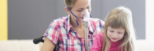 Mulher com máscara de oxigênio e cadeira de rodas lendo um livro com a garotinha