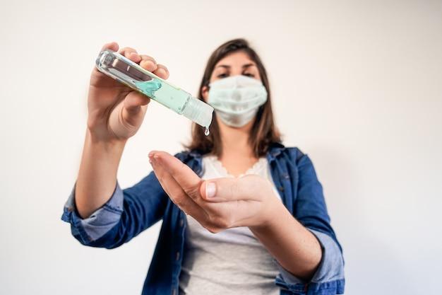 Mulher com máscara de proteção médica colocando anti-séptico.