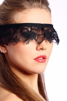 Mulher com máscara de renda preta sobre o rosto
