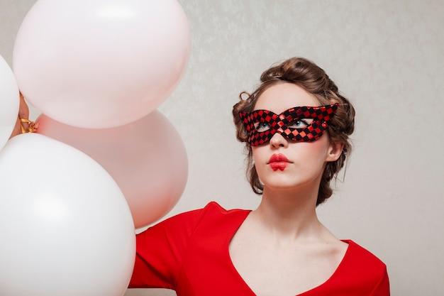 Mulher com máscara e vestido vermelho com balões