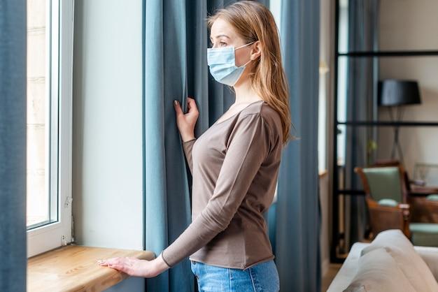 Mulher com máscara em quarentena, olhando para as janelas