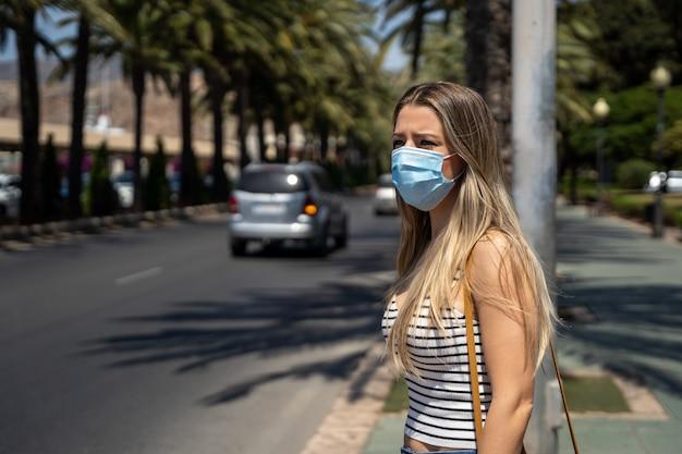 Mulher com máscara facial andando pela cidade durante a pandemia de coronavírus