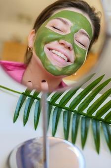 Mulher com máscara facial ao olhar no espelho