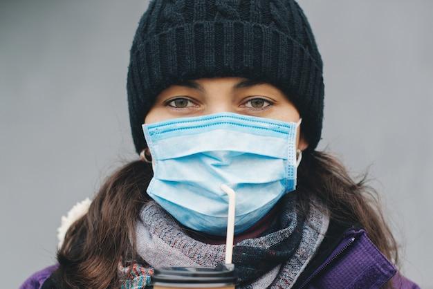 Mulher com máscara facial bebe café ao ar livre. epidemia de coronavírus na cidade. máscara protetora para disseminação de coronavírus.