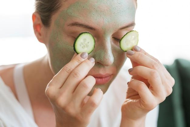 Mulher com máscara facial colocando fatias de pepino