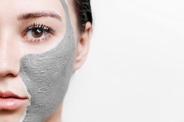 Mulher com máscara facial de argila para cuidados com a pele