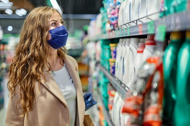 Mulher com máscara facial e luvas de borracha compra produtos de mercearia no supermercado.