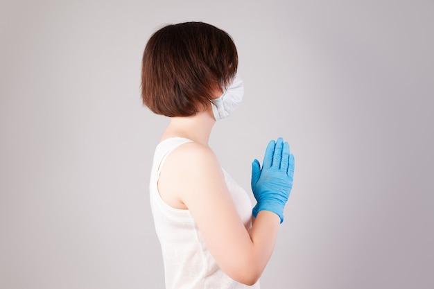 Mulher com máscara facial e luvas de nitrila na parede cinza, surto de doença coronavírus 2019 ou covid-19