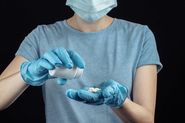 Mulher com máscara facial e luvas médicas segura um frasco de comprimidos na parede preta.
