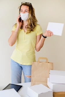 Mulher com máscara facial falando ao telefone