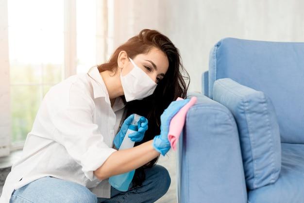 Mulher com máscara facial, limpando o sofá