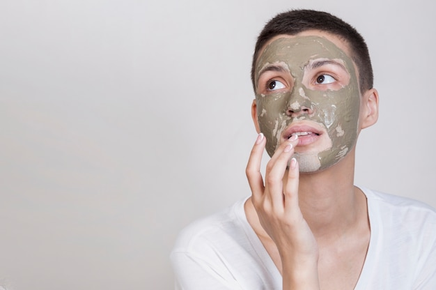 Mulher com máscara facial, olhando para cima