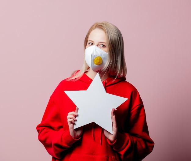Mulher com máscara facial padrão anti-poeira ffp2 segurando banner em formato de estrela em fundo rosa