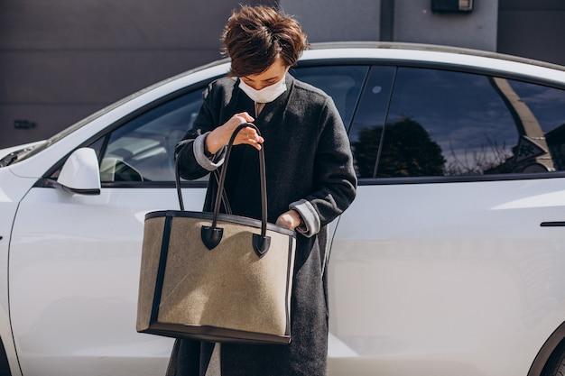 Mulher com máscara facial parada ao lado do carro