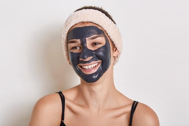 Mulher com máscara facial preta no rosto, olhando para o lado com um sorriso encantador