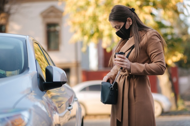 Mulher com máscara facial preta segura o copo de café perto do carro e olha a chave do carro. carro aberto de mulher. protectiv