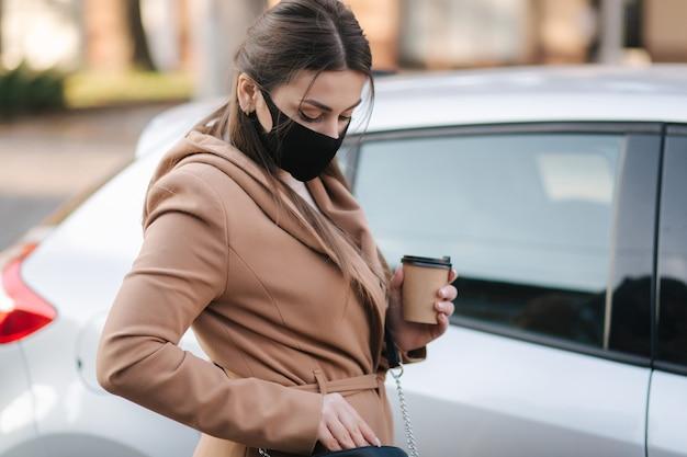 Mulher com máscara facial preta segura o copo de café perto do carro e olha a chave do carro.