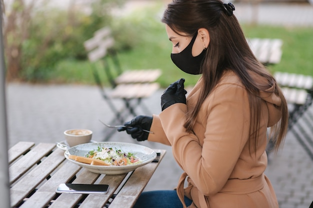 Mulher com máscara facial preta sentada no café e preparada para comer salada vegana. conceito de café de quarentena. covid19.