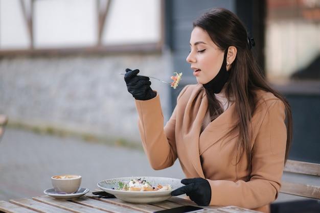 Mulher com máscara facial preta sentada no café e preparada para comer salada vegana.