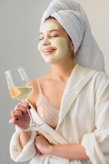 Mulher com máscara facial segurando copo de vinho