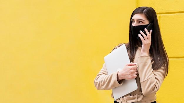 Mulher com máscara facial segurando laptop e falando no smartphone