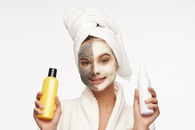 Mulher com máscara facial segurando sprays cosméticos Foto Premium