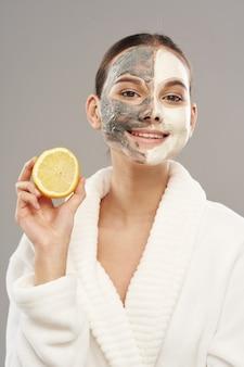 Mulher com máscara facial segurando um limão