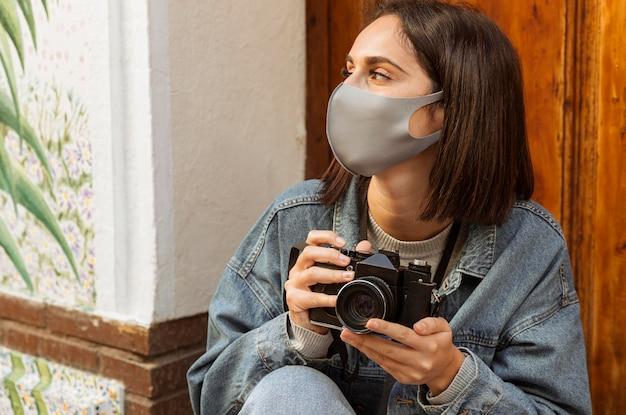 Mulher com máscara facial segurando uma câmera