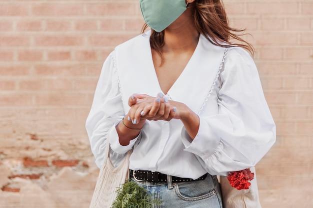 Mulher com máscara facial usando desinfetante para as mãos