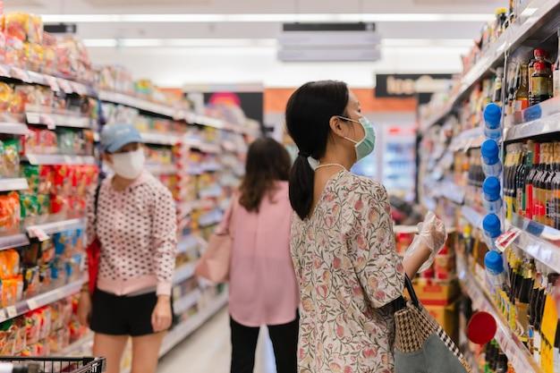 Mulher com máscara facial usando luvas enquanto faz compras em um supermercado durante a quarentena de covid19